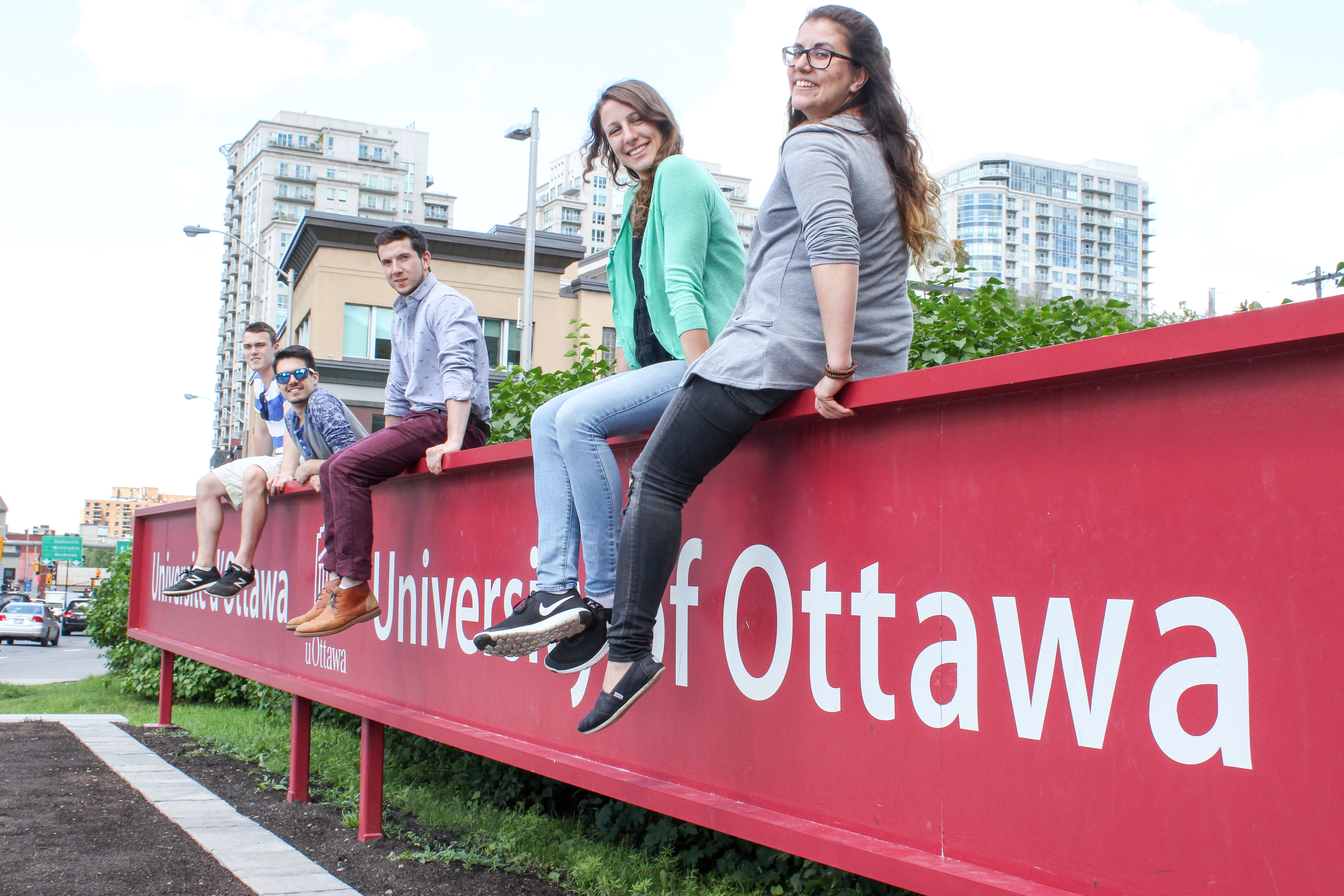 Students sitting on UOttawa sign